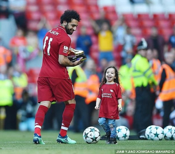 a group of baseball players playing a football game: Salah's four-year-old daughter ran on to kick the ball around the Anfield pitch on Sunday