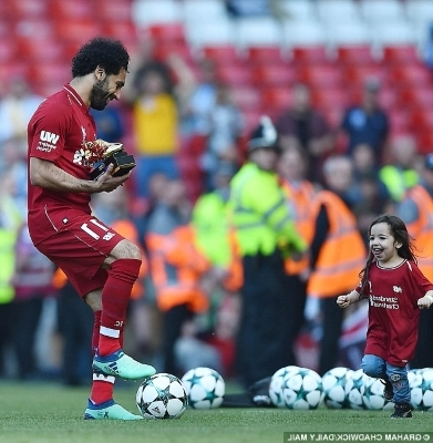 a group of baseball players playing a football game: The Liverpool star cheekily stole the ball off her but passed it back after jokingly being booed