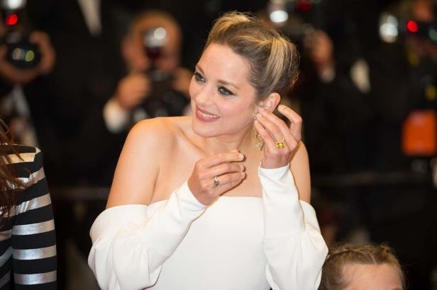 Diapositive 3 sur 11: Cannes - Marion Cotillard loses her earrings on the Red Carpet