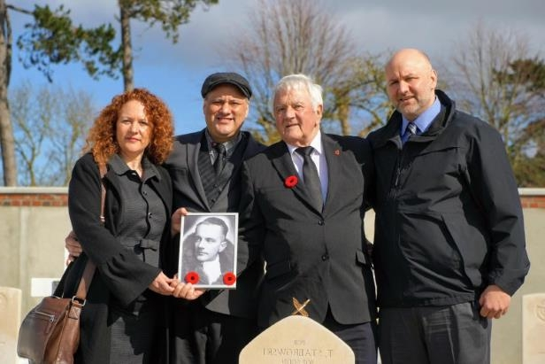 a group of people posing for the camera: From left to right, Michael Melaney stands with his father Andre Melaney, brother Mark Melaney and sister Andrea Chambers at Tadeusz Stabrowski's reburial ceremony in France.
