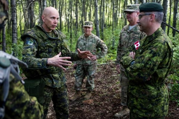 a group of people standing next to a man in a military uniform: Lt.-Gen. Wayne Eyre, right, who was a brigadier general at the time of this photo, speaks with Lt.-Gen. Paul Wynnyk, commander of the Canadian army, left, in the Wainwright Garrison training area in 2016. Eyre has now been appointed deputy commander of the UN Command in Korea.