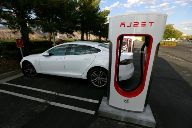 a car parked on the side of a road: Tesla Inc. designs and manufactures electric vehicles, charging stations, battery packs and more.
