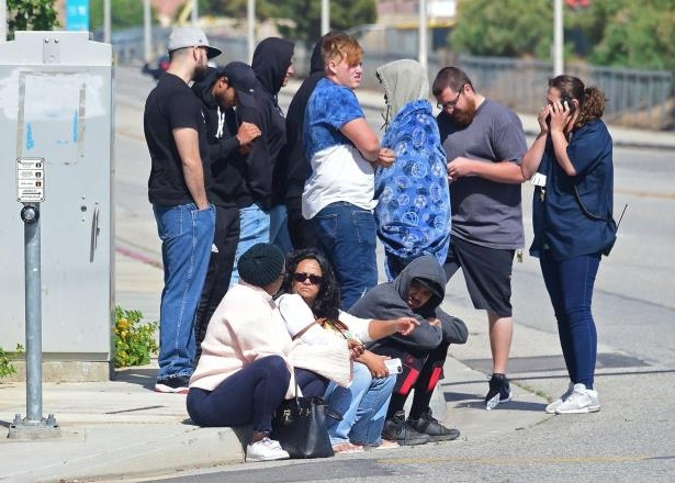 a group of people on a sidewalk: People wait following reports of the shooting at Highland High School.