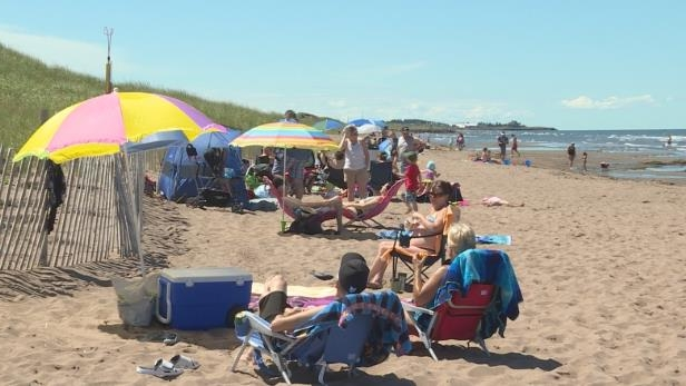 a group of people sitting at a beach: Aboiteau Beach becomes the first Blue Flag-certified New Brunswick beach.
