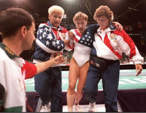 a group of people standing around each other: US gymnast Kerri Strug (2nd L) screams in pain as