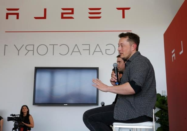a man holding a sign: Elon Musk, CEO of Tesla Motors Inc., left, discusses the company's Gigafactory on Tuesday, July 26, 2016.