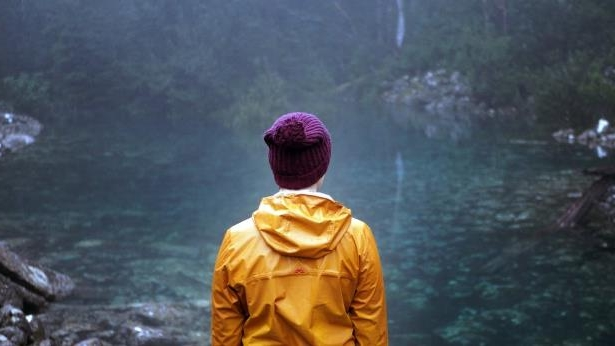 A woman wearing a yellow raincoat and a beanie stands in front of the tarn: The tarn is increasingly popular among visitors