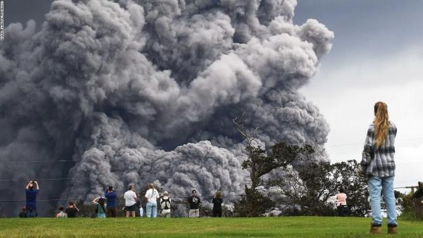 People watch at a golf course as an ash plume rises in the distance from the Kilauea volcano on Hawaii's Big Island .