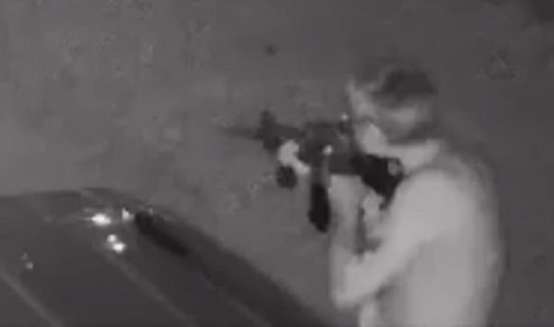 a blurry photo of a person: A man identified by police as 51-year-old Barry Freeman can be seen preparing to fire an AR-15 rifle at police officers during a May 11 incident in Evansville, Indiana, in which he and a neighbor were killed.