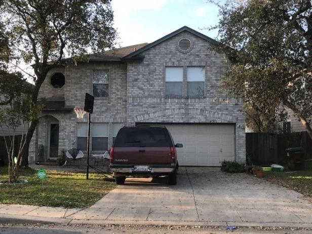 a car parked in front of a house: Bexar County Sheriff's Office deputies say 11 people were arrested Friday, March 16, 2018, at this residence and charged with cruelty to livestock animals in what the office called a possible animal sacrifice.