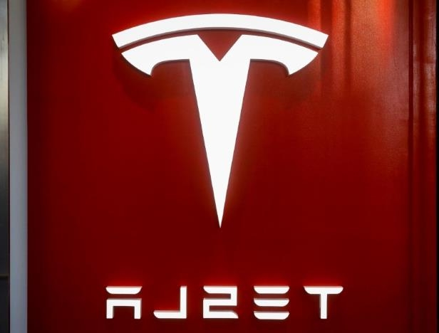 a close up of a sign: The Tesla logo is seen at the entrance to Tesla Motors' new showroom in Manhattan's Meatpacking District in New York City