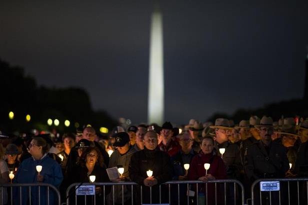 a group of people standing in front of a crowd: Law enforcement officers hold candles during the National Law Enforcement Officers Memorial Fund 30th annual Candlelight Vigil.