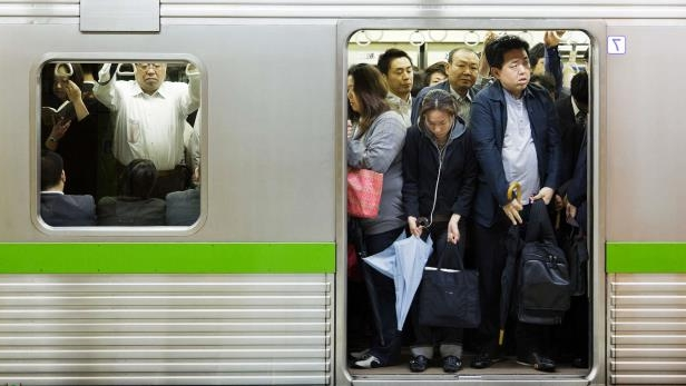 a group of people standing on a subway train: Train apps can tell you how full carriages will be.