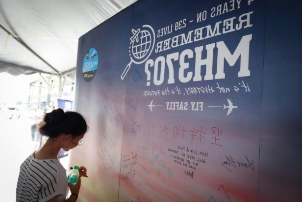 a man and text: A girl writes a condolence message during the Day of Remembrance for MH370 in Kuala Lumpur, Malaysia, marking the fourth anniversary of the jet's March 8, 2014, disappearance.