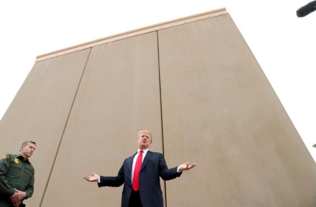 a man standing in front of a building: U.S. President Trump participates in tour of U.S.-Mexico border wall prototypes near Otay Mesa Port of Entry in San Diego, California
