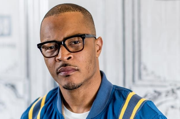 a man wearing glasses and smiling at the camera: T.I.