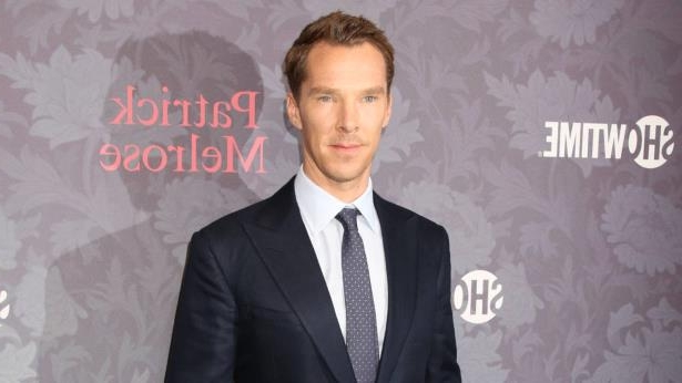 Benedict Cumberbatch wearing a suit and tie standing in front of a sign