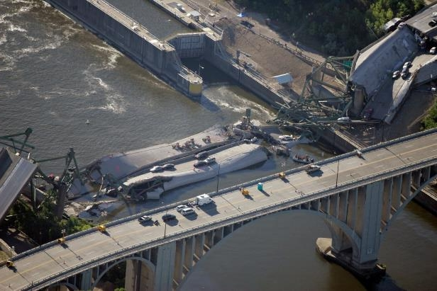 Slide 1 of 13: The Interstate-35W freeway bridge is seen collapsed in the Mississippi River in downtown Minneapolis, Thursday, Aug. 2, 2007. Divers searched the Mississippi River Thursday for more bodies entombed in cars trapped beneath the twisted steel and concrete slabs of a bridge that collapsed Wednesday, killing at least four.