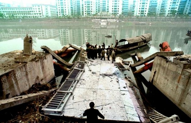 Slide 5 of 13: Chinese officials examine the edge of the collapsed Rainbow Bridge over Qijiang River in Chongqing, China Wednesday, Jan. 6, 1999. The bridge collapsed Monday, killing 39 people. Chinese authorities have detained the building contractor of the bridge pending an investigation.