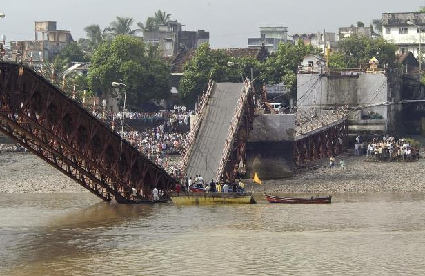 Slide 7 of 13: People gather to see rescue work near a collapsed bridge in Daman, 190 kilometers (120 miles) north of Bombay, India, Friday, Aug. 29, 2003. At least 12 people, including eight school children, were killed Thursday when a school van, two rickshaws and motorcycles plunged into a river after the concrete bridge collapsed in western India.