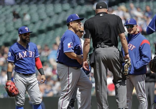 Texas Rangers starting pitcher Bartolo Colon, second from right, smiles as he returns to the mound after talking with a Rangers' trainer after Colon was hit by a ball hit by Seattle Mariners shortstop Jean Segura during the fourth inning of a baseball game, Wednesday, May 16, 2018, in Seattle. (AP Photo/Ted S. Warren)