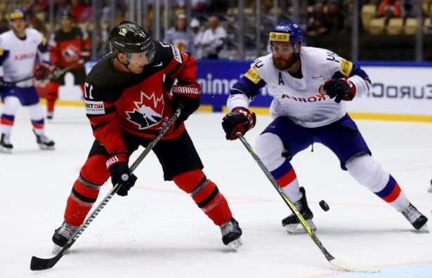 a hockey game in the snow: Korea's Alex Plante and Canada's Jaden Schwartz of Canada battle for the puck during a group stage game at the hockey world championships. Schwartz will miss the remainder of the tournament due to an upper-body injury.