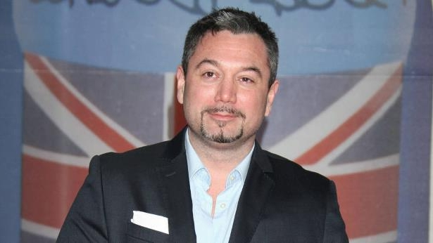 Huey Morgan wearing a suit and tie smiling at the camera