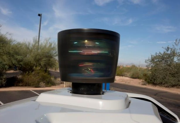 a car on the side of a road: FILE PHOTO: The lidar sensor is seen on a self driving Volvo vehicle, purchased by Uber, Phoenix, Arizona
