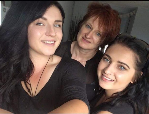 a couple of people posing for the camera: Ann Wittenberg (centre) with her daughters Rachel, 21, (left) and Victoria Emon, 23, (right). The 52-year-old mother of three died Sunday in Tofino after a surfing accident, according to her brother. Her son Josh is missing from the picture.