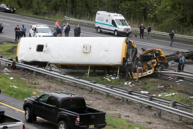 FILE - In this May 17, 2018, file photo, emergency personnel work at the scene of a school bus and dump truck collision on Interstate 80 in Mount Olive, N.J. Hudy Muldrow Sr., the school bus driver caused the fatal crash by crossing three lanes of traffic in an apparent attempt to make an illegal U-turn, according to a criminal complaint released Thursday, May 24, that charged him with vehicular homicide.