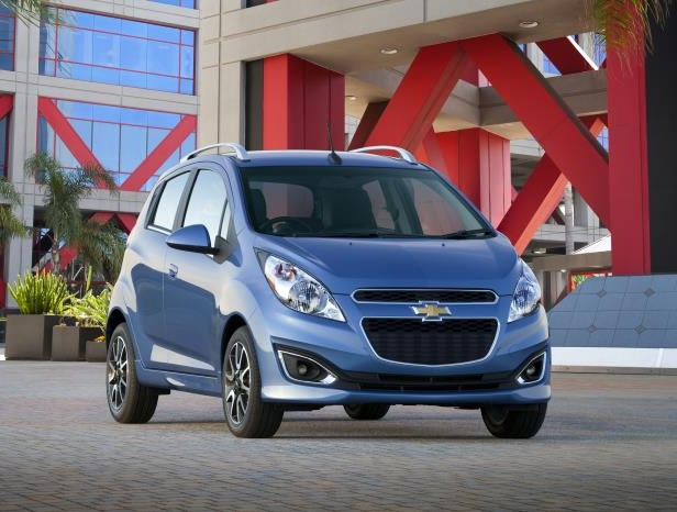 a blue car parked in front of a building: 2013 Chevrolet Spark
