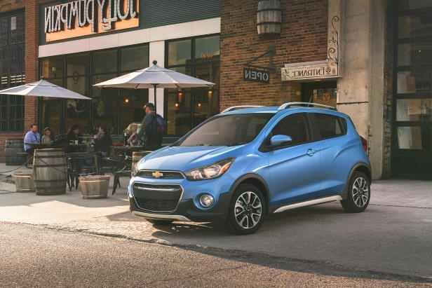 a blue car parked in front of a building: The 2017 Chevrolet Spark ACTIV is a sportier take