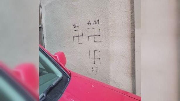 a close up of text on a red surface: Swastikas were drawn in permanent marker on the exterior walls of the Chess Piece Cafe over the weekend,