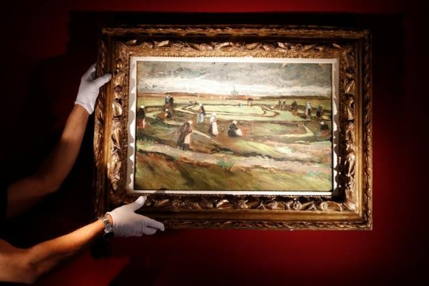 An Artcurial employee poses as he holds the painting 'Raccommodeuses de filets dans les dunes, 1882' (Women Mending Nets in the Dunes) by Vincent Van Gogh during a preview for media at their auction house in Paris.