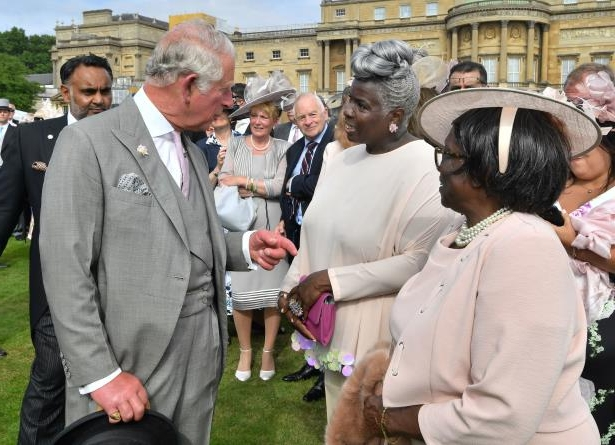 The Prince of Wales meets Kingdom Choir conductor Karen Gibson and her mother at a Royal Garden Party at Buckingham Palace, London.