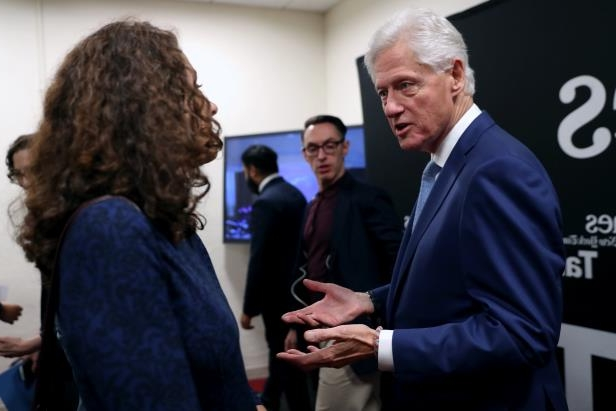 Bill Clinton et al. standing next to a man in a suit and tie: Former President Bill Clinton fielded questions regarding Monica Lewinsky, the special counsel's inquiry and other topics at a TimesTalk event in New York on Tuesday night.