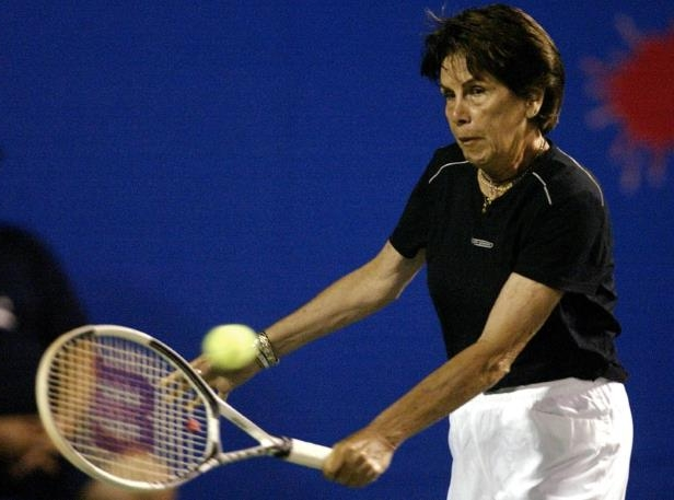 a man hitting a ball with a racket: FILE PHOTO: Former Brazilian great Maria Ester Bueno, winner of 19 Grand Slam singles and doubles titles from 1959-68, plays during a tennis exhibition on Copacabana beach in Rio de Janeiro