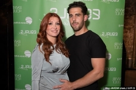 a person posing for the camera: Dazzling: Showing off her burgeoning bump, the radiant redhead donned a grey midi dress with wrap around detailing across the chest that hugged her pregnancy curves