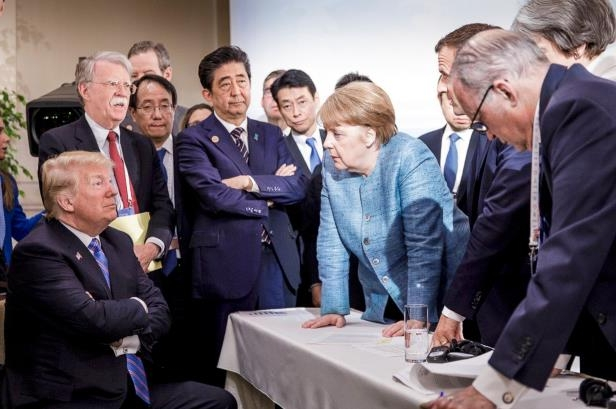 Shinzo Abe et al. standing around a table: German Chancellor Angela Merkel spoke with President Trump during the Group of 7 summit meeting on Saturday. The photo quickly went viral.