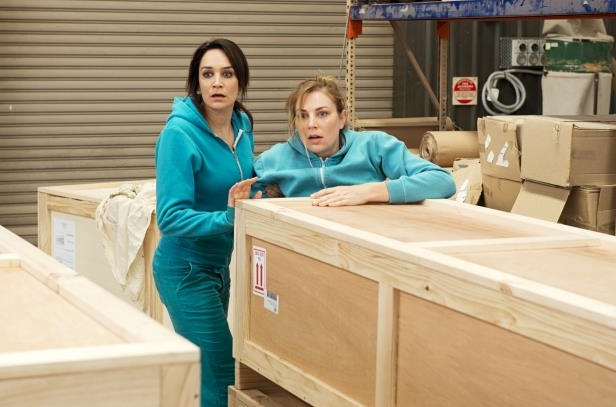 a woman sitting in a box: Allie and Frankie planned to use the crates to escape.