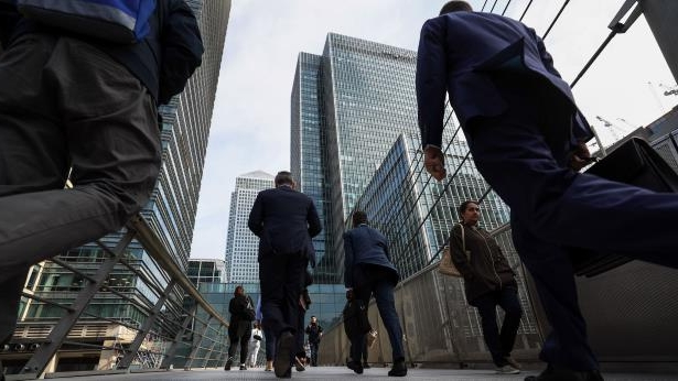 Shift in resources: operational roles, such as the 20,000 at Citi, face elimination as banks embrace machine labour: Pedestrians cross a footbridge towards the Canary Wharf business, financial and shopping district in London, U.K., on Thursday, June 5, 2018. The owners of a Canary Wharf skyscraper leased to Citigroup Inc. are seeking to refinance the 661 million-pound ($882 million) loan used to buy it five years ago, two people with knowledge of the plan said. Photographer: Chris Ratcliffe/Bloomberg