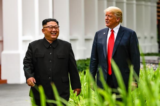 Slide 1 of 64: U.S. President Donald Trump and North Korea leader Kim Jong Un walk from their lunch at the Capella resort on Sentosa Island Tuesday, June 12, 2018 in Singapore.