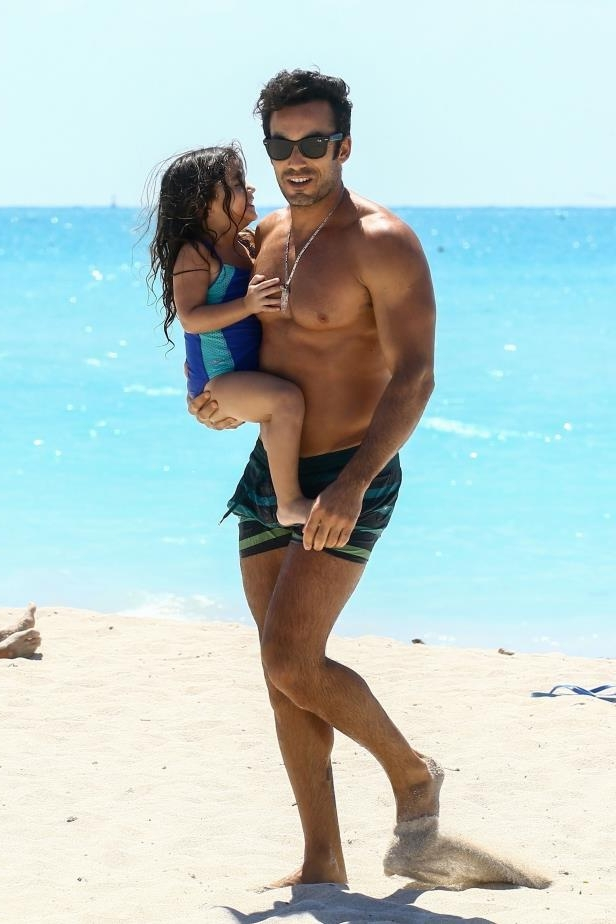 Slide 33 of 67: Mexican actor Aaron Diaz carried his daughter on the beach in Miami on March 23.