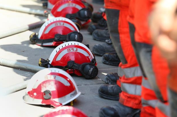 Tower block fire in London: Firefighters lay their helmets on the ground as they observe a minute's silence near to Grenfell Tower (Jonathan Brady/PA)