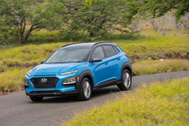 a blue car driving on a road: 2018 Hyundai Kona