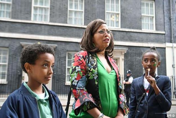 a couple of people that are standing in front of a building: Judith Zacharias (centre) with her children Soliana and Alexander, who were some of the 40 or 50 children who planted shrub and some bulbs Prime Minister Theresa May on Tuesday