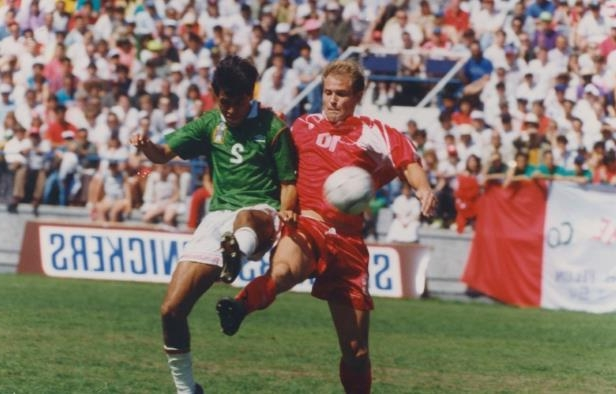 a group of football players on a field: Canadian John Catliff, left, clashes with a Mexican defender during a World Cup qualifier in Toronto in 1993.