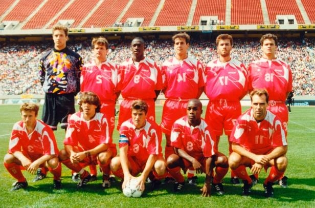 a group of football players posing for a photo: Team Canada poses for a picture on the pitch at Commonwealth Stadium in Edmonton ahead of the first leg of its two-game playoff against Australia in 1993.