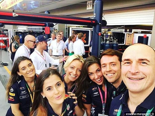 a group of people posing for a photo: Ms Horbass (centre) poses for a selfie with colleagues on pit lane at the Singapore Grand Prix