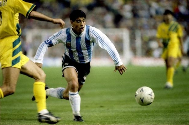 a group of young men playing a game of football: Argentina's Diego Maradona in action against Australia in the two teams' 1993 win-or-go-home two-game playoff.